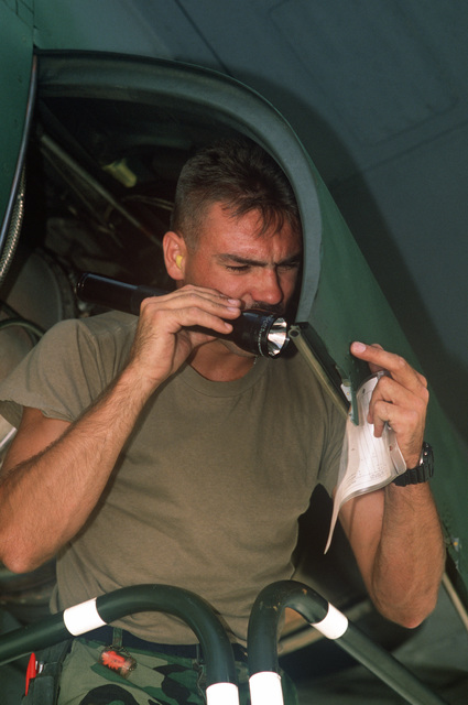 Sergeant Mark F. Cory of the of the 314th Tactical Airlift Wing of Little Rock Air Force Base, Arkansas, inspects an engine panel on his AIRLIFT RODEO '90 team's C-130E Hercules transport aircraft during the maintenance competition. AIRLIFT RODEO is an annual airdrop competition that tests the flight and ground skills of Military Airlift Command aircrews as well as foreign teams.