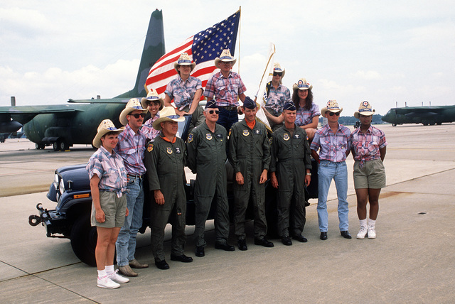 The Airlift Rodeo '90 welcoming committee members are, front, left to right, SGT Gloria Tate, SGT David Evans, COL D. E. Sowata, BGEN James Melvin, COL Maxwell C. Bailey, BGEN James L. Cole Jr., SGT Willie Wellbrook and A1C Dominique Collins. On the vehicle, are, left to right, A1C Angela Hebb, SRA Jennifer Weisman, Terry Miller and SGT Amy Smith. Airlift Rodeo is an annual competition of the Military Airlift Command.