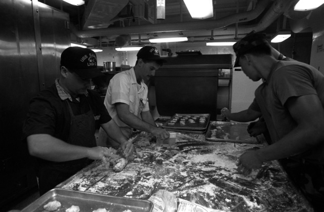 Navy and Marine mess management specialists aboard the amphibious assault ship USS SAIPAN (LHA 2) make cookies in preparation for the arrival of evacuees from the U.S. Embassy in Monrovia, Liberia. The SAIPAN is on station off the coast of Liberia FOR Operation Sharp Edge