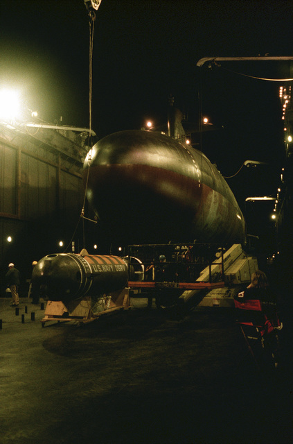 """Set lights illuminate the nuclear-powered attack submarine USS PERMIT (SSN 594) during the filming of the movie """"The Hunt for Red October."""" The movie is being filmed on US Navy installations and uses active-duty sailors as extras"""