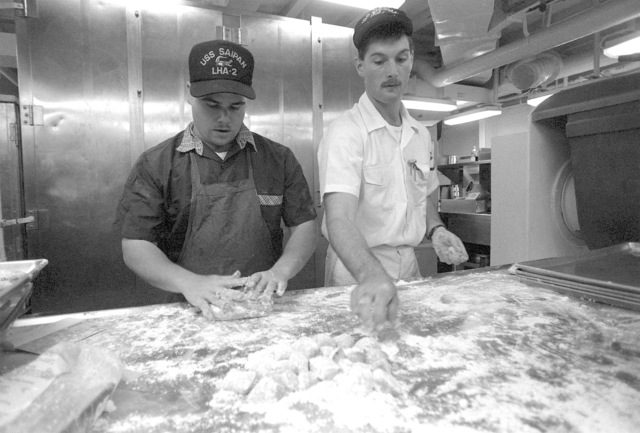 Two mess management specialists aboard the amphibious assault ship USS SAIPAN (LHA-2) make cookies in preparation for the arrival of evacuees from the U.S. Embassy in Monrovia, Liberia. The SAIPAN is on station off the coast of Liberia for OPERATION SHARP EDGE