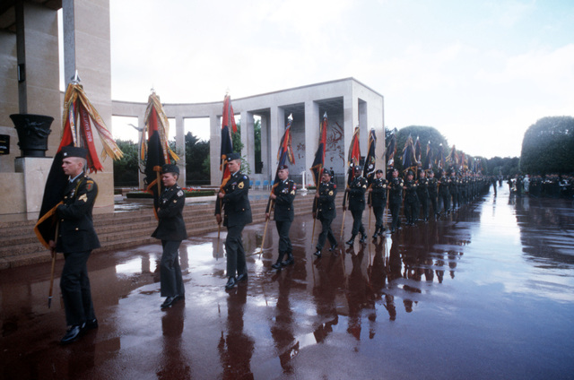 Representatives of the U.S. Army divisions that took part in the Allied invasion of France carry their units' colors into the amphitheater at the Normandy American Cemetery during an official wreath-laying ceremony held to mark the 45th anniversary of the Allied invasion