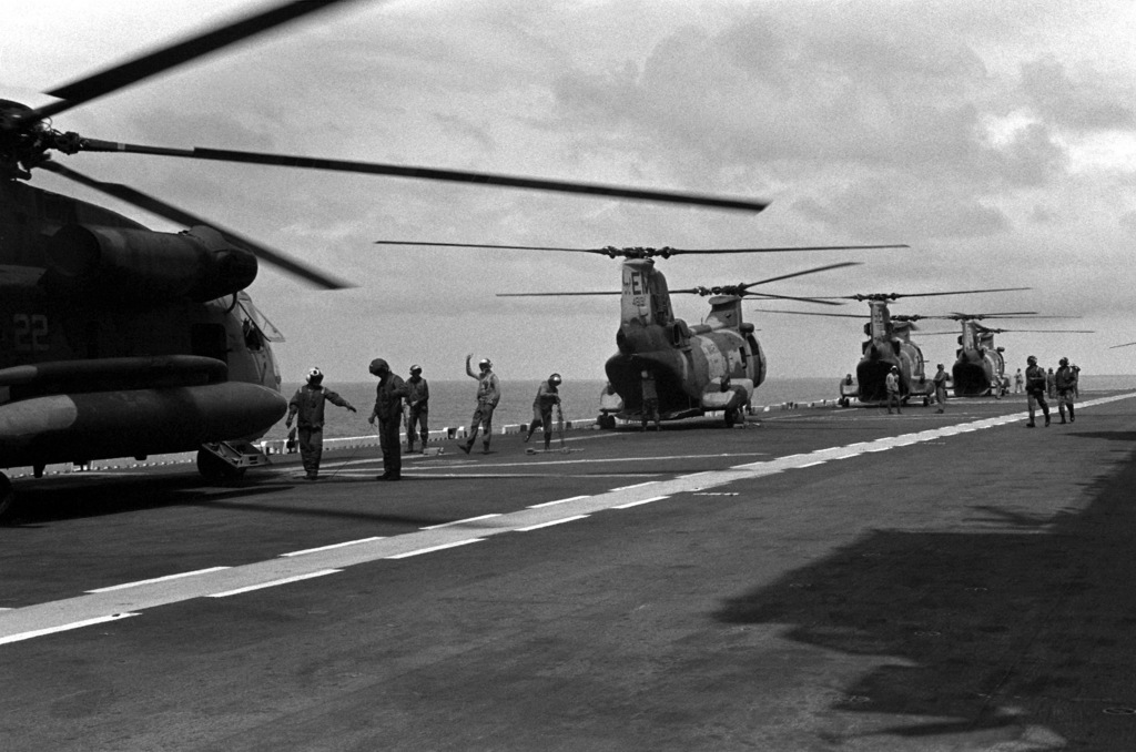 A CH-53D Sea Stallion helicopter attached to Marine Medium Helicopter Squadron 261 (HMM-261), left, and three CH-46E Sea Knight helicopters of HMM-261 start up their engines on the flight deck of the amphibious assault ship USS SAIPAN (LHA 2) during a rehearsal for Operation Sharp Edge. The SAIPAN is on station off the coast of Liberia