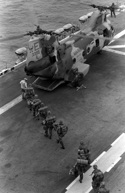 Marines of the 22nd Marine Expeditionary Unit (22nd MEU) are led to a Marine Medium Helicopter Squadron 261 (HMM-261) CH-46E Sea Knight helicopter aboard the amphibious assault ship USS SAIPAN (LHA 2) during a rehearsal for Operation Sharp Edge. The SAIPAN is on station off the coast of Liberia