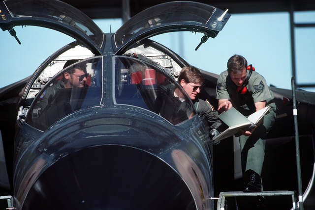 CPT Chuck Simpson, left, listens as CPT Mike Masters and SSGT Timothy Warner discuss relevant items in the aircraft's data book prior to taking an F-111E aircraft up on a test flight. Simpson and Masters are assigned to the 2874th Test Squadron
