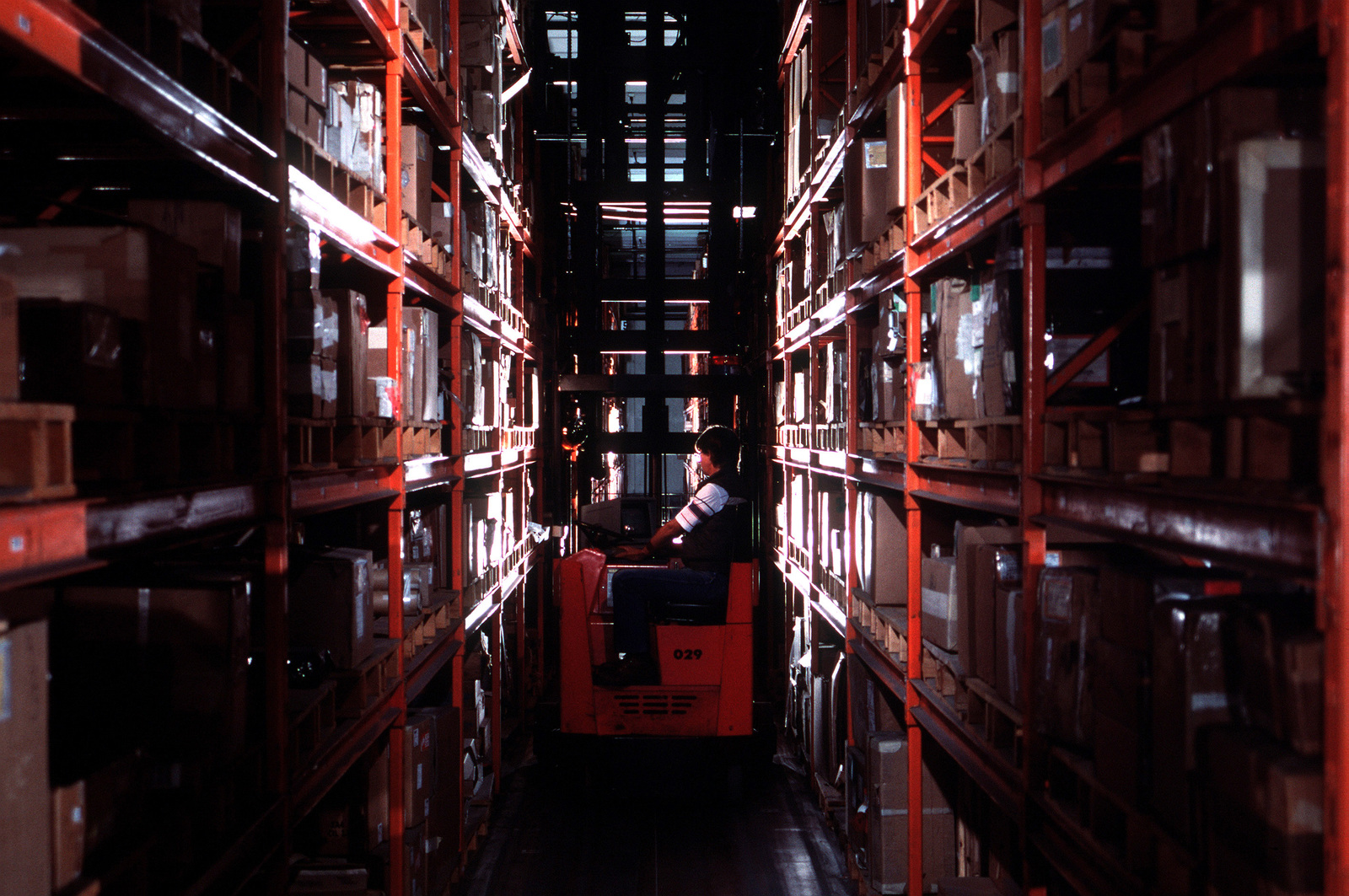 Gerald Graunstadt files and retrieves items in an automated warehouse using a computerized forklift. When positioned over wires in the floor, each forklift is able to determine its current position and move to the location of a desired item