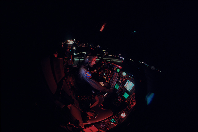 MAJ Stephen R. Webber of the 2874th Test Squadron runs through a cockpit check before taking an F-111 aircraft on a night test flight