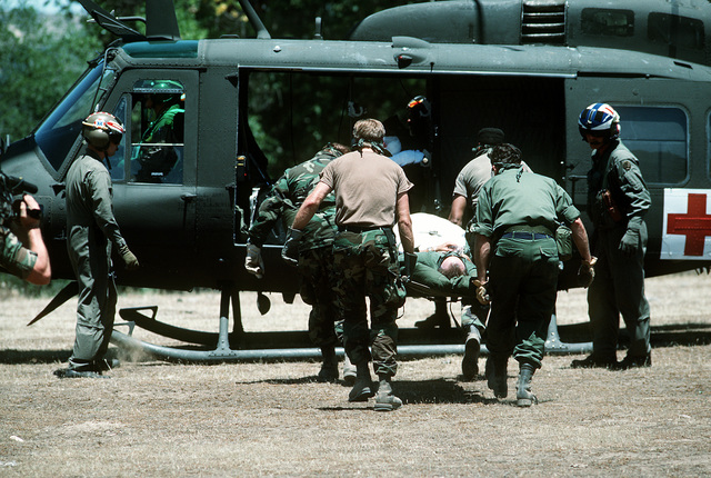Air Force medical personnel transport a simulated patient to an Army UH-1 Iroquois helicopter for evacuation during Exercise Patriot Spirit '90, an exercise providing training for active and reserve Air Force and Army medical units under battlefield conditions.