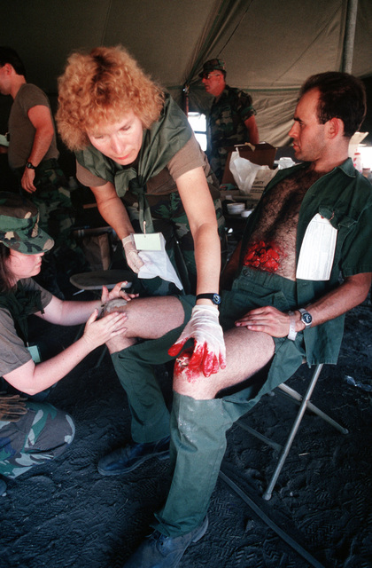 LTC Kathleen Corsiglia, standing, and SGT Terry C. Davis use moulage to practice medical techniques on SPC James Wade during exercise Patriot Spirit '90, an exercise providing training for active and reserve Air Force and Army medical units under battlefield conditions.