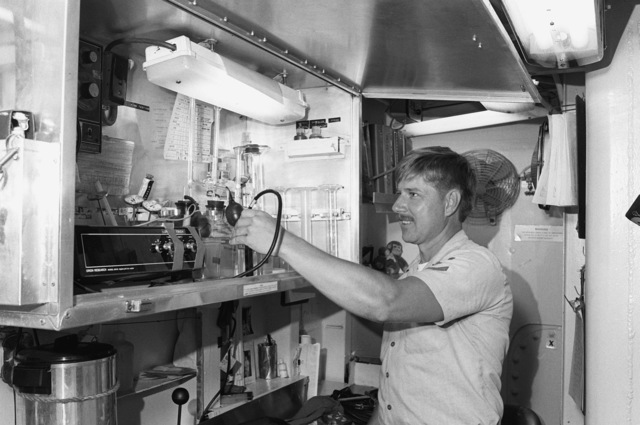 Boiler Technician 3rd Class (BT3) Jeff Truett checks an oil sample aboard the frigate USS TRUETT (FF-1095). BT3 TRUETT is the son of CHIEF PETTY Officer Quincy H. Truett, the ship's namesake, who was posthumously awarded the Navy Cross for valor in action while serving in Vietnam
