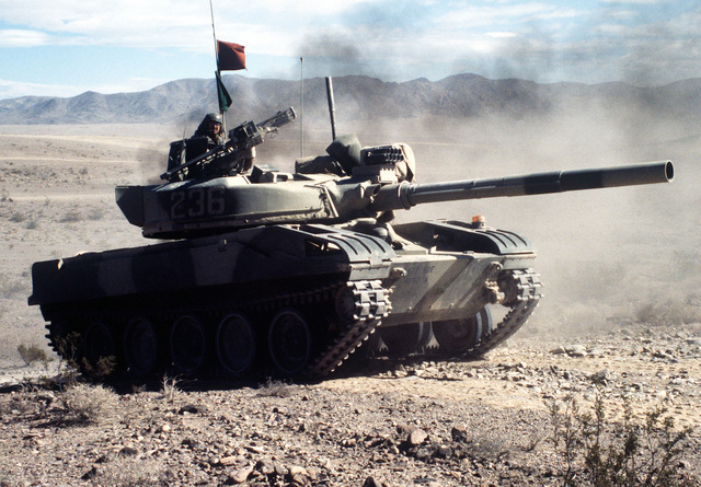 An Opposing Forces (OpFor) M-551 Sherdian light tank visually modified to resemble a Soviet T-72 main battle tank moves across the desert to join the attack on the Blue Forces during an exercise