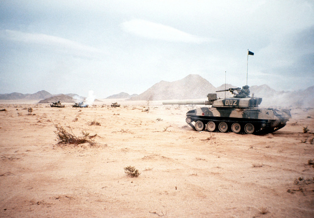 An Opposing Forces (OpFor) M-551 Sherdian light tank visually modified to resemble a Soviet T-72 main battle tank moves to join up with several other OpFor vehicles on the move to attack the Blue Forces during an exercise