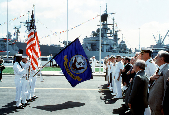 Officers and other guests honor the flag during the station's opening day ceremonies.  The guided missile cruiser USS DALE (CG-19), one of several ships in port during the event, is moored in the background
