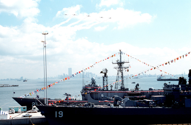 Pennants and bunting decorate the guided missile frigate USS FLATLEY (FFG-21) and the guided missile cruiser USS DALE (CG-19), docked at the pier during the station's opening day ceremonies.  Aircraft fly in formation overhead in honor of the event