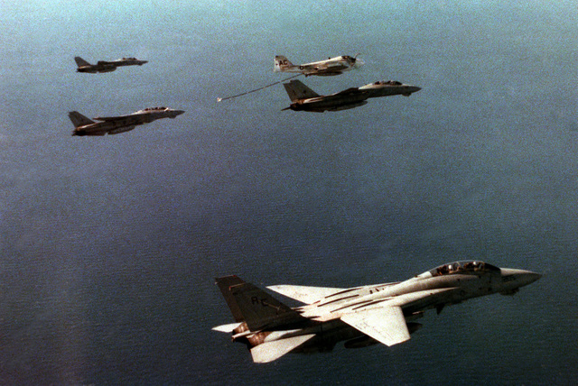 As his wing man holds position ahead, a Fighter Squadron 14 (VF-14) F-14A Tomcat aircraft moves in to receive fuel from an Attack Squadron 75 (VA-75) KA-6D Intruder aircraft. The aircraft are flanked by two Figher Squadron 32 (VF-32) Tomcat aircraft, upper left and lower right. All five aircraft are assigned the aircraft carrier USS JOHN F. KENNEDY (CV 67) which can be seen just to the left of the Intruder aircraft