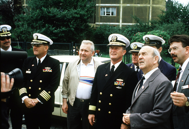 John Davis, United States (US) ambassador to Poland; Rear Admiral Thomas D. Paulsen, Commander, Cruiser Destroyer Group 2; Captain (CAPT) Gary Zwirschitz and other officers are filmed by a cameraman as they gather for a ceremony at a Polish memorial. The Navy representatives are visiting Poland during a port call by two US vessels, the guided missile cruiser USS HARRY E. YARNELL (CG 17) and the guided missile frigate USS KAUFFMAN (FFG 59). The visit represents the first port call by US vessels since 1927, is taking part in conjunction with BALTOPS '90, a NATO exercise in the Baltic Sea
