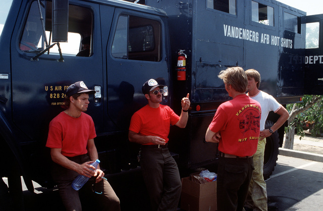 """Firefighters from the Vandenburg Air Force Base fire department, known as the """"Hot Shots,"""" take a break in the shade of their truck at a staging area near Dos Pueblos High School. The firefighters are joining units from state and local agencies in battling the brush fires that are sweeping through the area"""