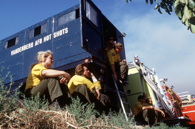"""Firefighters from the Vandenburg Air Force Base fire department, known as the """"Hot Shots,"""" take a break at a staging area near Dos Pueblos High School. The firefighters are joining units from state and local agencies in battling the brush fires that are sweeping through the area"""