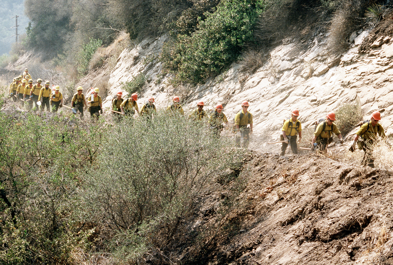 "Firefighters from the Vandenburg Air Force Base fire department, known as the ""Hot Shots,"" march along a road to reach one of the brush fires that swept through the area"
