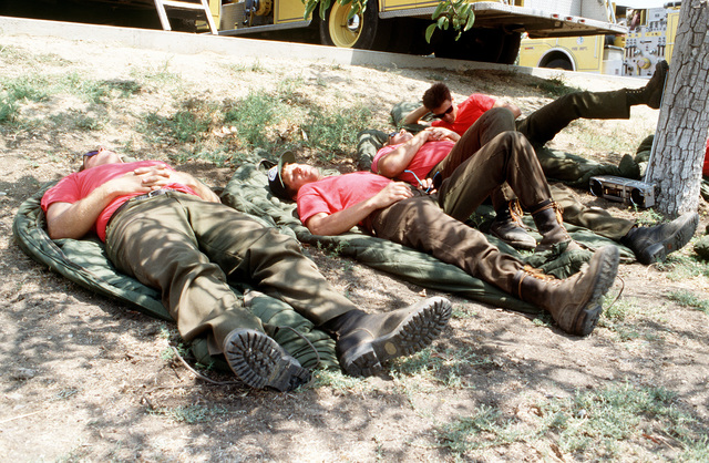 """Firefighters from the Vandenburg Air Force Base fire department, known as the """"Hot Shots,"""" take a break under a tree at a staging area near Dos Pueblos High School. The firefighters are joining units from state and local agencies in battling the brush fires that are sweeping through the area"""