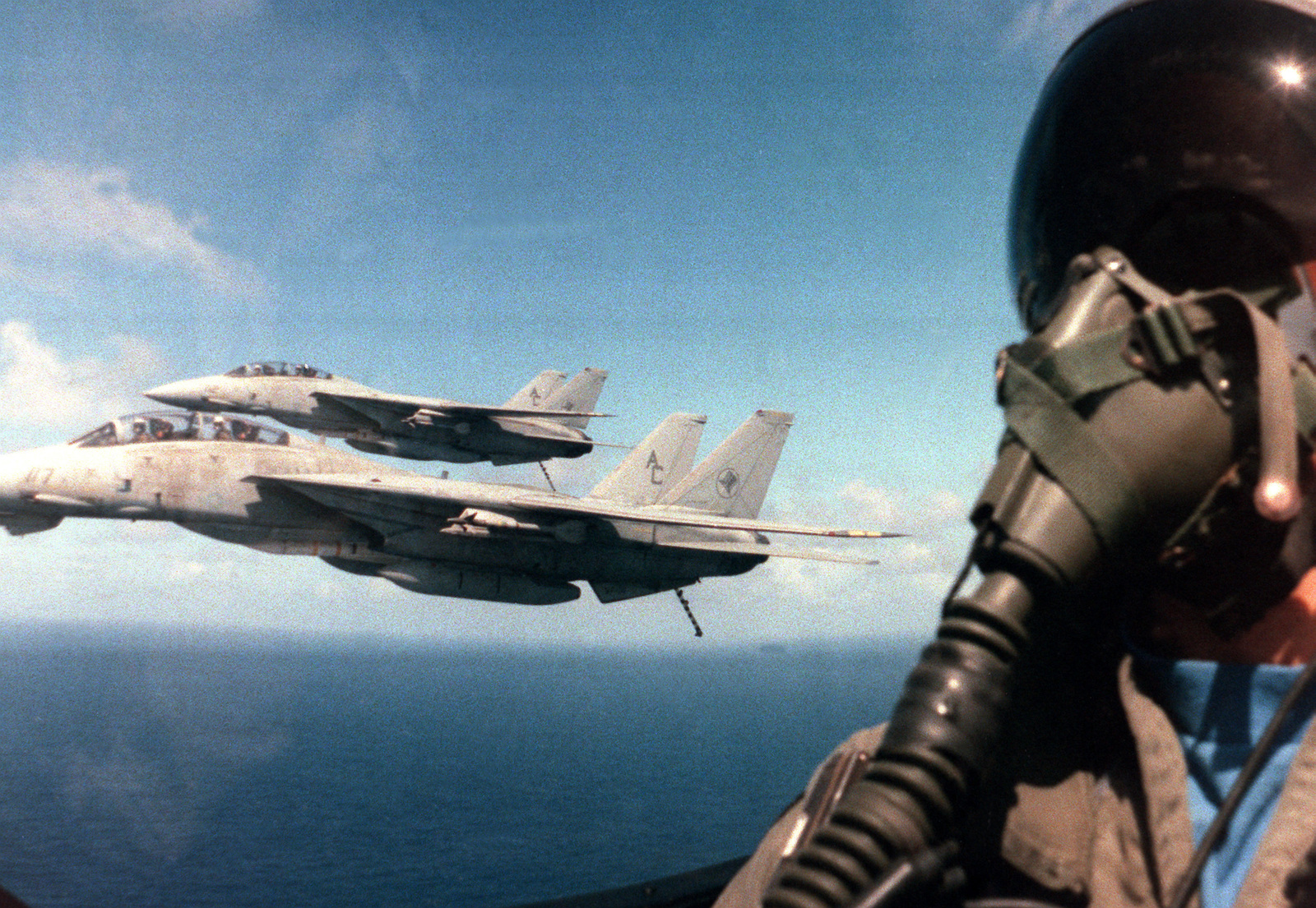 A close-up view of the pilot of an A-7E Corsair II aircraft, as he pilots his plane alongside two Fighter Squadron 14 (VF-14) F-14A Tomcat aircraft. The planes are returning to the aircraft carrier USS JOHN F. KENNEDY (CV 67)