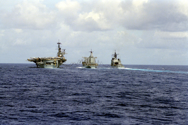 A stern view of the fleet oiler USS CIMARRON (AO-177), center, conducting underway replenishment with the aircraft carrier USS INDEPENDENCE (CV-62), left, and the guided missile cruiser USS ANTIETAM (CG-54) during WesPac '90
