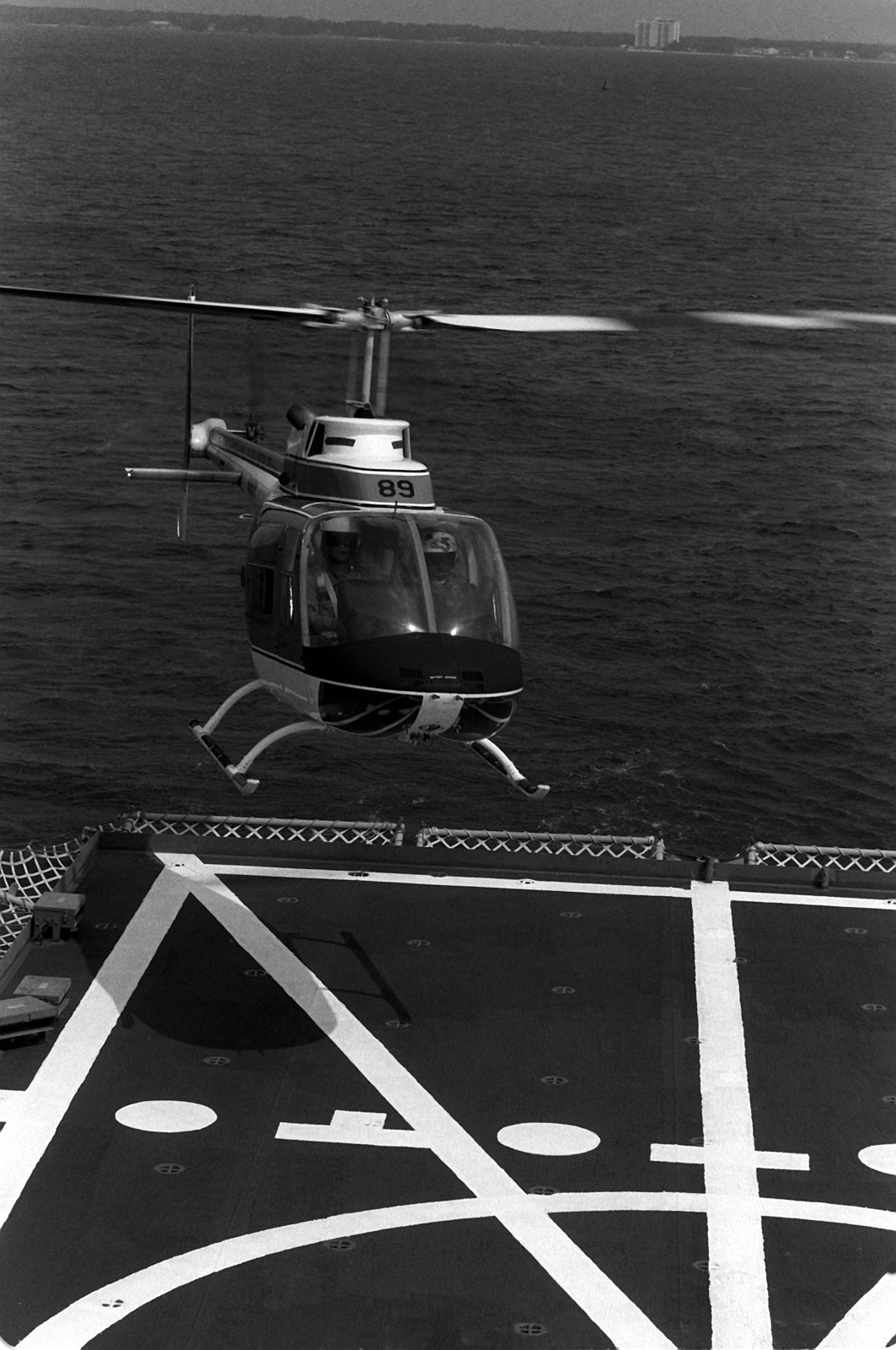 A Training Wing 5 (TAW-5) TH-57 Sea Ranger helicopter hovers over the flight deck of the helicopter landing trainer IX-514. The trainer, a converted harbor utility craft, is based at Naval Air Station, Pensacola, Florida