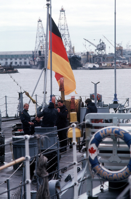 Crew members gather near the stern of the West German destroyer FGS LUTJENS (D-185) while the ship lies tied up in port. A portion of the Canadian frigate HMCS MARGAREE (DDH-230) is in the foreground