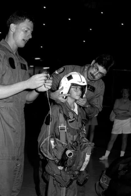 """ENS Dave Waterman, Training Squadron 86 (VT-86) demonstrates survival equipment as LTJG Nick Nickels, Training Squadron 4 (VT-4) helps 10-year-old Kathryne Drlicka with her helmet. Kathryne is one of many youngsters taking part in the National Museum of Naval Aviation's """"Adventure Deck Program. In addition to such equipment demonstrations by student naval flight officers from area training squadrons, the program also features simulators and flight gear displays, engine models, and flag and pennant exhibits"""