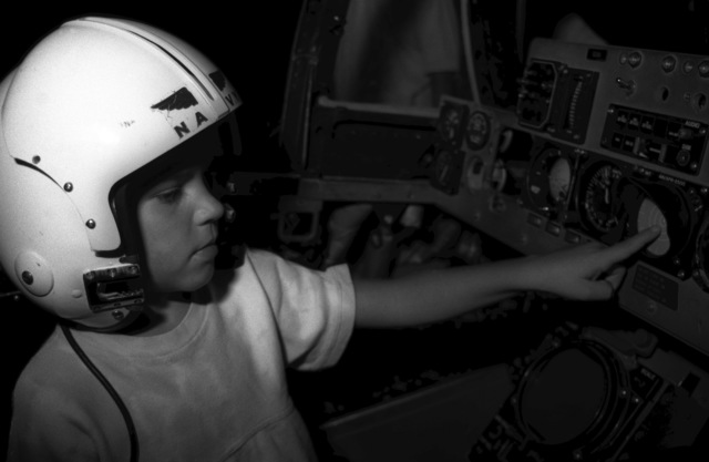 """Micheal Drlicka inspects the instrument panel in an F-4 Phantom II aircraft cockpit simulator at the National Museum of Naval Aviation's """"Adventure Deck."""" In addition to simulators and flight gear displays, the Adventure Deck Program features engine models, flag and pennant exhibits, and equipment demonstrations by student naval flight officers from area training squadrons"""