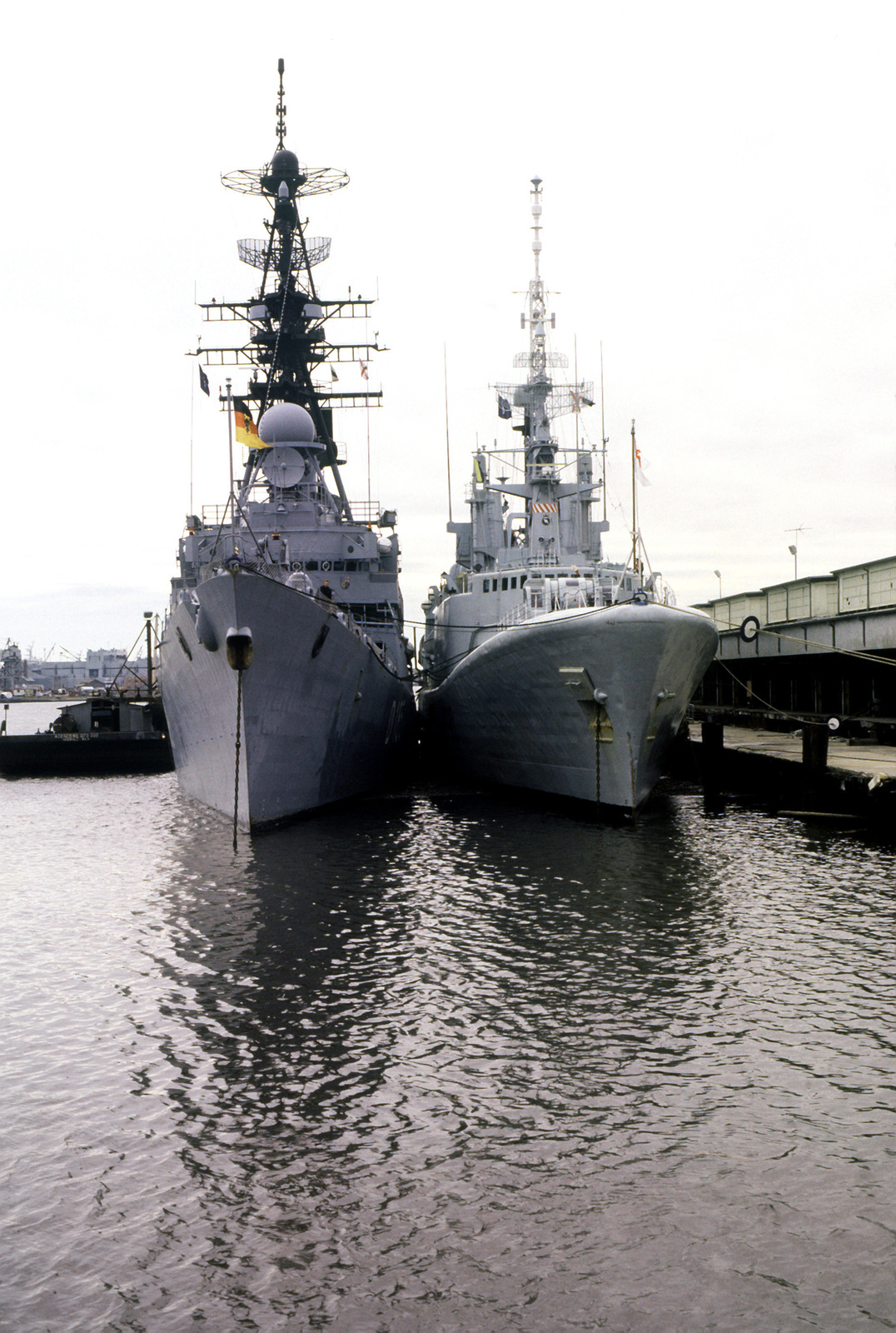 The West German destroyer FGS LUTJENS (D-185), left, and the Canadian frigate HMCS MARGAREE (DDH-230) lie tied up together in port