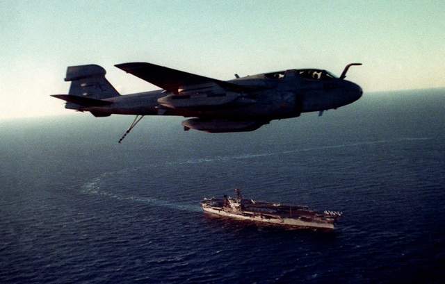 An EA-6B Prowler aircraft from Tactical Electronic Warfare Squadron 130 (VAQ-130) flies past the aircraft carrier USS JOHN F. KENNEDY (CV 67) during FLEET EX 90