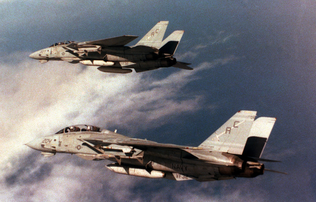 Two Fighter Squadron 32 (VF-32) F-14A Tomcat aircraft bank into a turn as they return to the aircraft carrier USS JOHN F. KENNEDY (CV 67) at the end of FLEET EX 90