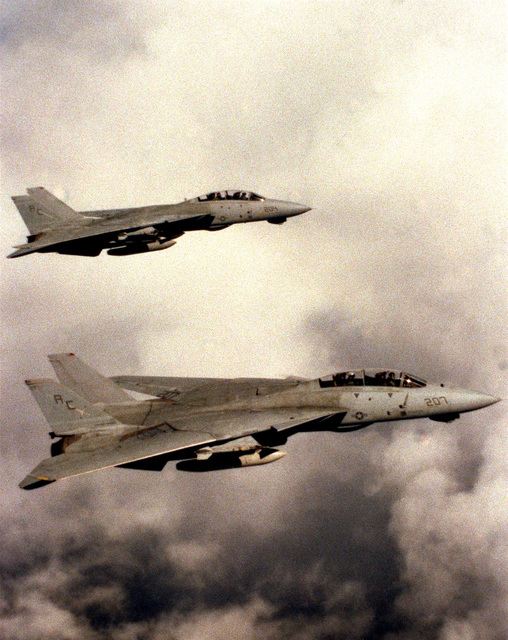 Two Fighter Squadron 32 (VF-32) F-14A Tomcat aircraft fly through the clouds as they return to the aircraft carrier USS JOHN F. KENNEDY (CV 67) at the end of FLEET EX 90