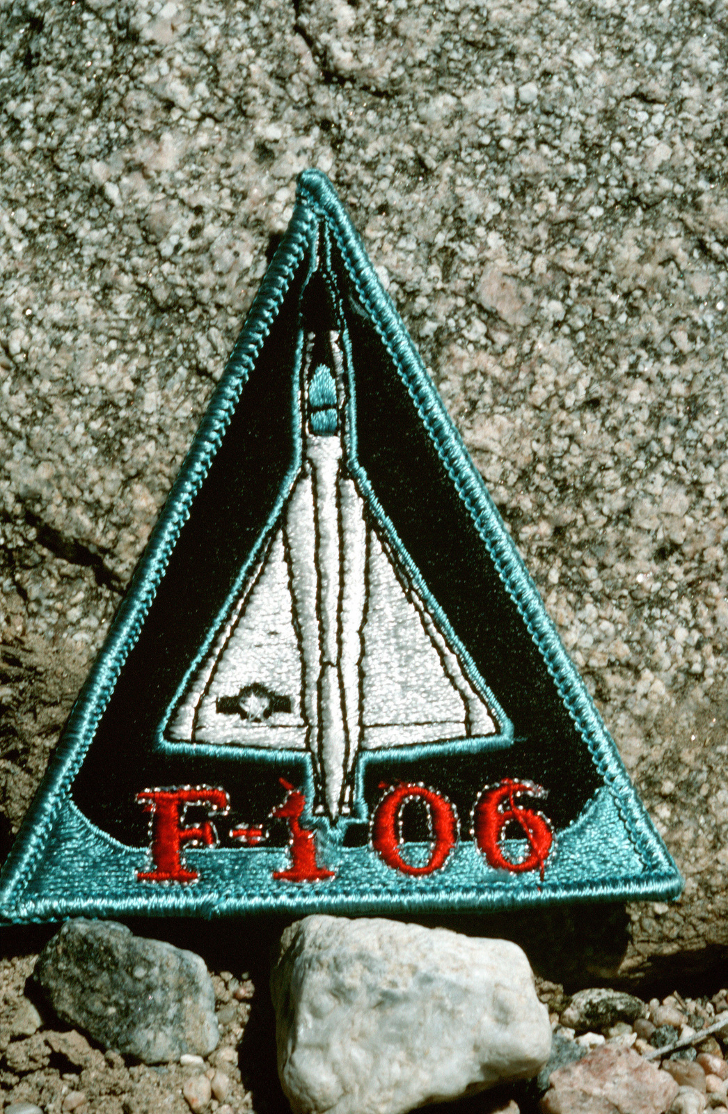 A close-up view of a patch with an F-106 Delta Dart aircraft embroidered on it