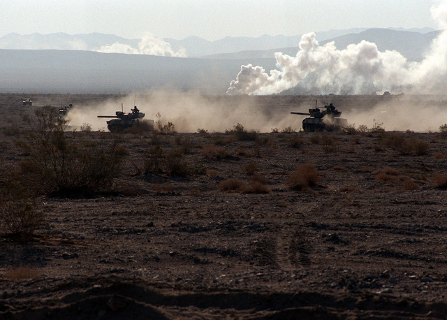 Two Opposing Forces (OpFor) M-551 Sheridan light tanks visually modified to resemble Soviet T-72 main battle tanks advance through the desert to join the attack on the Blue Forces during an exercise