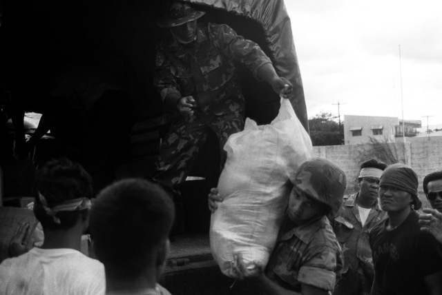 A Filipino soldier hands a bag of food to LCPL R.F. Schranz of the 7th Communications Battalion during the relief effort for civilians trapped in remote area following the earthquake of July 16, 1990