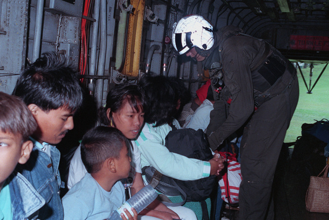 LCPL Shackleford, first mechanic aboard a Marine Heavy Helicopter Squadron 363 (HMH-363) CH-53D Sea Stallion helicopter, buckles a Filipino woman into her seat as an evacuation flight prepares to depart with Filipinos left homeless by the earthquake of July 16, 1990