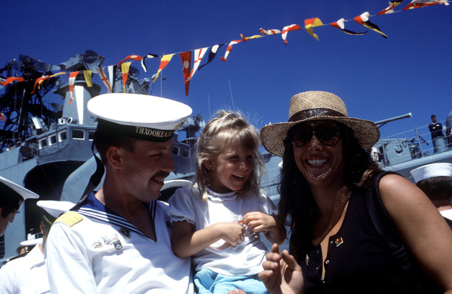 A Soviet sailor shares a laugh with a child and her mother as they stand on the pier in front of the Soviet guided missile destroyer ADMIRAL VINOGRADOV. Three ships of the Soviet Pacific Fleet are in San Diego for a five-day goodwill visit
