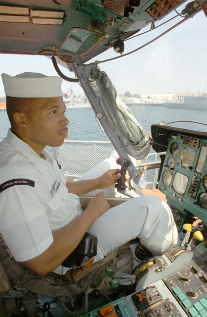 An American sailor checks out the cockpit of a Soviet Ka-27 Helix helicopter during an open house aboard one of the three Soviet Pacific Fleet ships that are in San Diego for a five-day goodwill visit. All three ships are open to visitors during their time in port