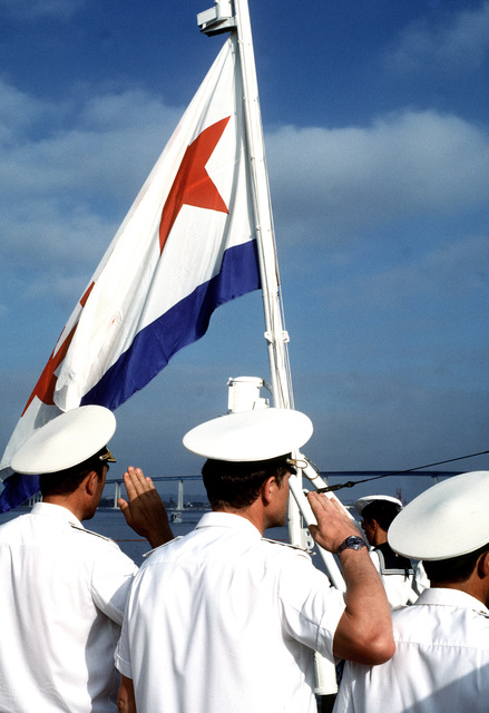 Soviet officers salute as the naval ensign is raised during a colors ceremony aboard one of the three Soviet Pacific Fleet ships that are in San Diego for a five-day goodwill visit