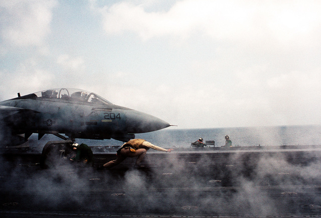 A catapult officer gives the signal to launch a Fighter Squadron 21 (VF-21) F-14A Tomcat aircraft during flight operations aboard the aircraft carrier USS INDEPENDENCE (CV-62). The INDEPENDENCE is one of the U.S. Navy ships sent to the Persian Gulf in response to Iraq's invasion of Kuwait