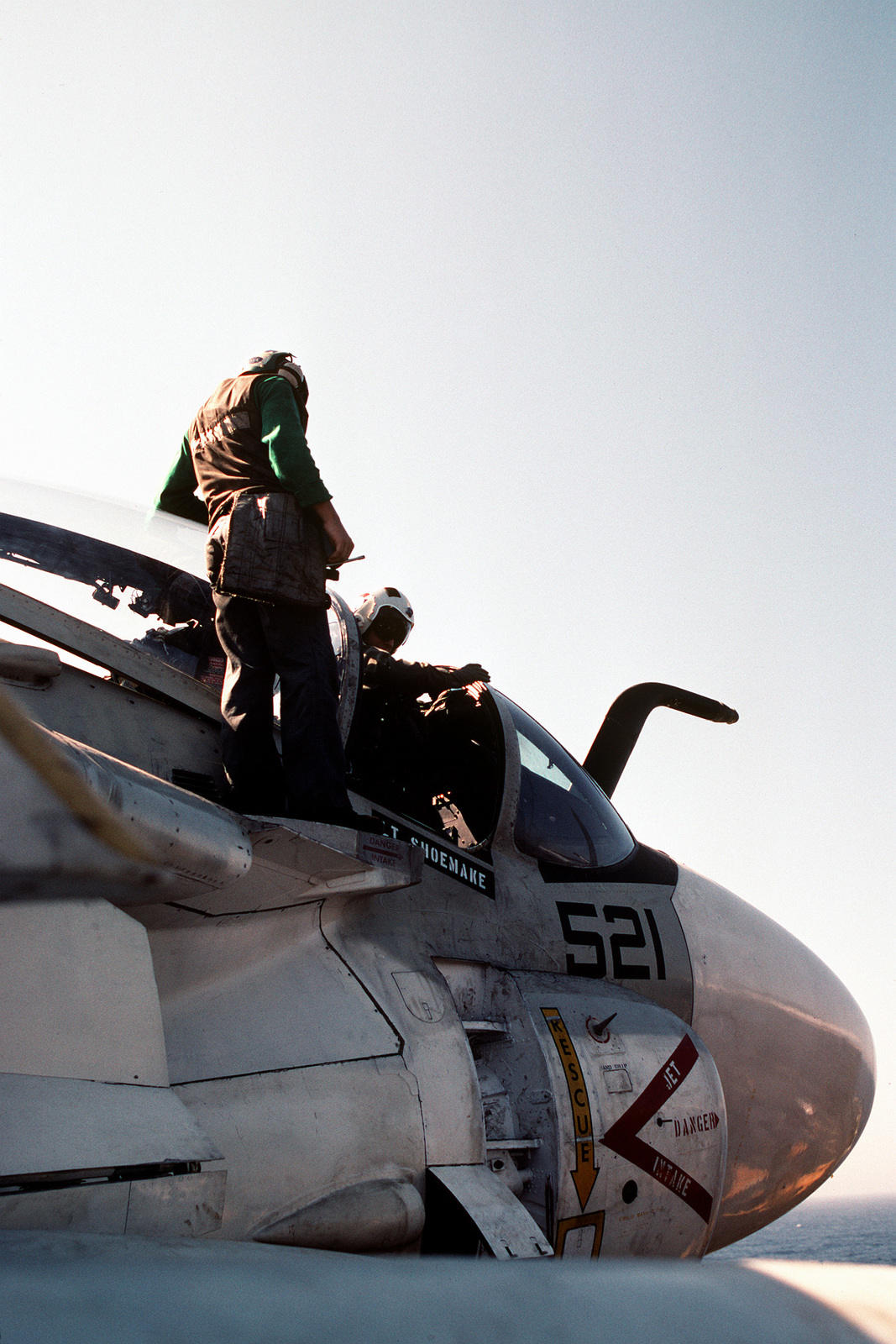 A maintenance crewman stands as an Attack Squadron 34 (VA-34) bombardier-navigator climbs into the cockpit of an A-6E Intruder aircraft on the flight deck of the nuclear-powered aircraft carrier USS DWIGHT D. EISENHOWER (CVN-69). The EISENHOWER is on station in the Persian Gulf in response to Iraq's invasion of Kuwait