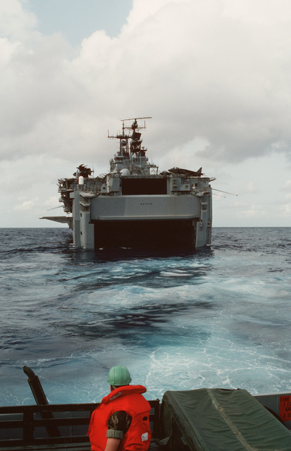 A Marine standing in the back of a truck aboard a landing craft looks toward the open well deck of the amphibious assault ship USS SAIPAN (LHA 2) during Operation Sharp Edge. Marines of the 22nd Marine Expeditionary Unit (22nd MEU) are being sent to the U.S. Embassy in Monrovia, Liberia, to augment security and evacuate U.S. and foreign nationals from the fighting between government and rebel forces