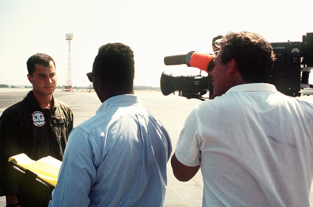 A Navy journalist conducts an interview with Lance CPL. Rick Elliott, a Marine reservist on active duty as an aircraft loadmaster with Marine Refueler-Transport Squadron 452 (VMGR-452), during Operation Desert Shield