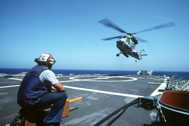 A sailor stands by with wheel chocks and tie-down chains as an SH-2F Seasprite helicopter of Light Helicopter Anti-submarine Squadron 34 (HSL-34) comes in to land aboard the guided missile cruiser USS TICONDEROGA (CG-47). The TICONDEROGA is on station in the Persian Gulf in response to Iraq's invasion of Kuwait