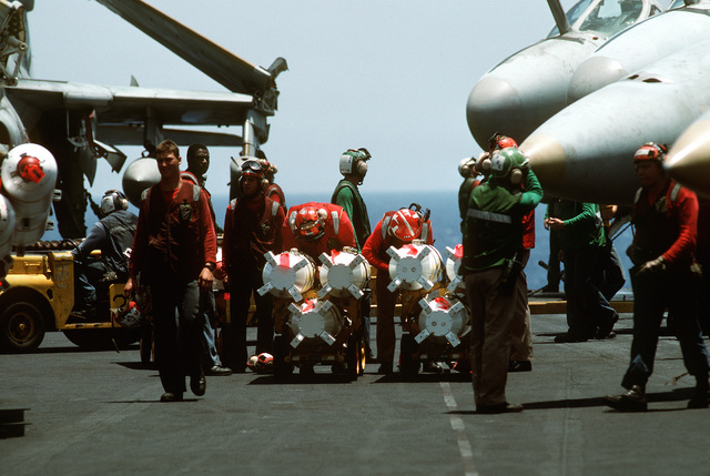 Aviation ordnancemen check the fuses on several Mark 20 Rockeye II cluster bombs before they are loaded aboard aircraft on the flight deck of the nuclear-powered aircraft carrier USS DWIGHT D. EISENHOWER (CVN-69) during Operation Desert Shield