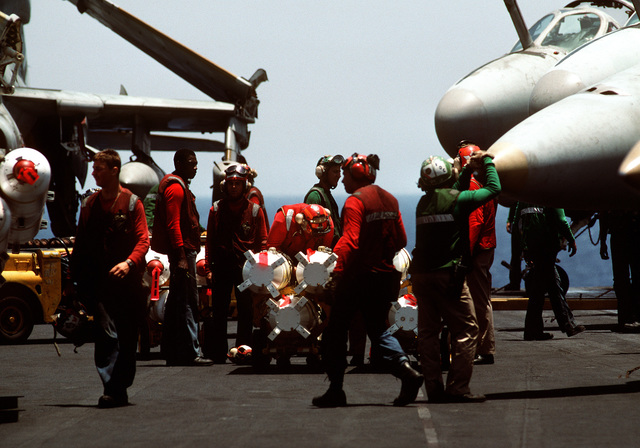 Aviation ordnancemen stand by to load Mark 20 Rockeye II cluster bombs onto one of the attack aircraft on the flight deck of the nuclear-powered aircraft carrier USS DWIGHT D. EISENHOWER (CVN-69). The EISENHOWER is on station in the Persian Gulf in response to Iraq's invasion of Kuwait