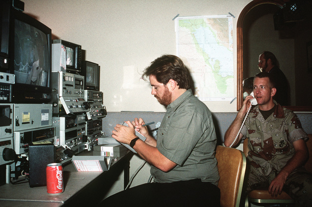CHIEF Warrant Officer 3 Chuck Henry of the Navy Broadcasting Service uses a telephone to relay background information as videotaped footage of Operation Desert Shield is sent via satellite to Washington, D.C., from the Joint Information Bureau
