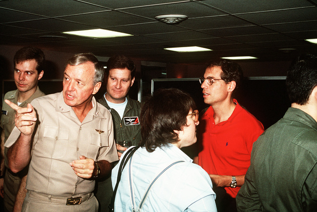 Rear Adm. Jerry L. Unruh, commander, Carrier Group 1, talks to media pool correspondents prior to a press conference aboard the aircraft carrier USS INDEPENDENCE (CV-62). The correspondents are covering Operation Desert Storm